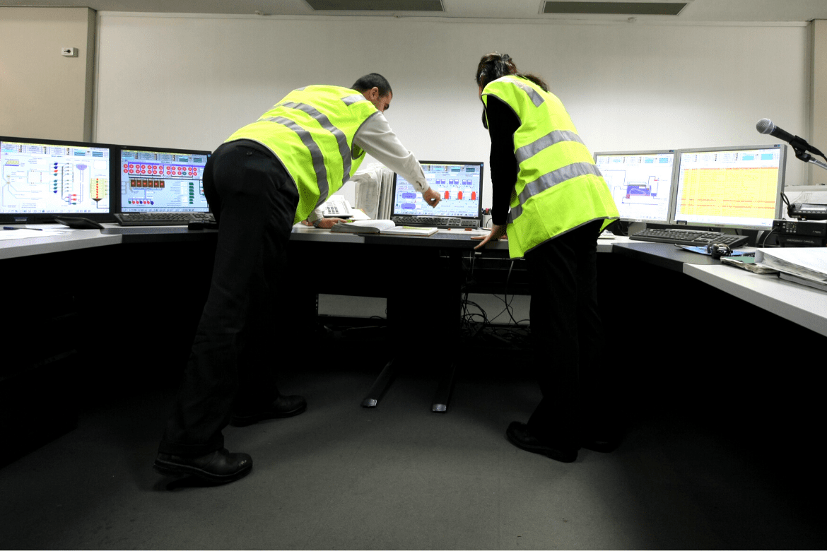 Man and woman in high Viz vests pointing at computer screens